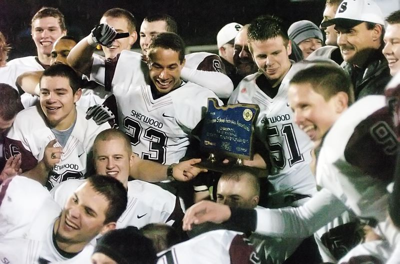 by: DAN BROOD - TROPHY TIME -- The Bowmen gather with the state championship trophy following Saturday's game.