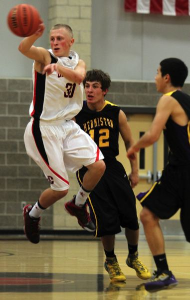 by: JONATHAN HOUSE - Clackamas junior Aaron Ahlstrom dishes off to a teammate in the Cavaliers season opener with Hermiston.