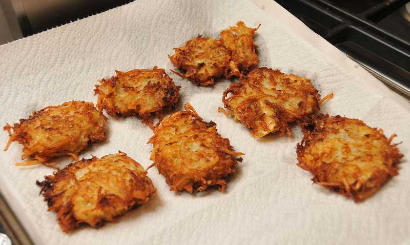 by: REVIEW, TIDINGS PHOTO: VERN UYETAKE - Golden brown latkes cool off before being packed to transport to the Hanukkah feast.
