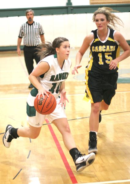 by: NEWS PHOTO: LOREN NIBBE - Junior guard Mackenzie Gipple drives down the court as a Cascade defender looks on.