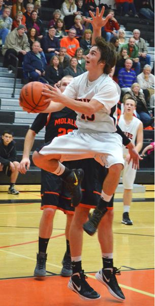by: JOHN BREWINGTON - Scappoose's Paul Revis drives the middle for a lay-in during last week's game with Molalla. The Tribe lost the game after leading.