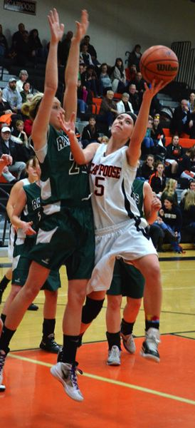 by: JOHN BREWINGTON - Scappoose's Haley Wight goes up for a shot during the first half with Estacada on Friday. Scappoose would end up losing the game by a point.