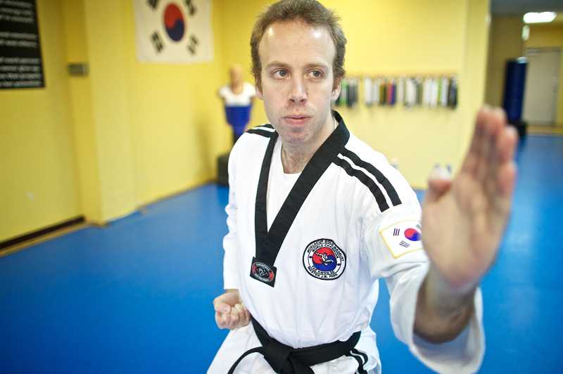 by: JAIME VALDEZ - Torryn Coufal who is developmentally disabled, practices forms at World Championship Taekwondo in Beaverton, where he successfully tested for his second-degree black belt.