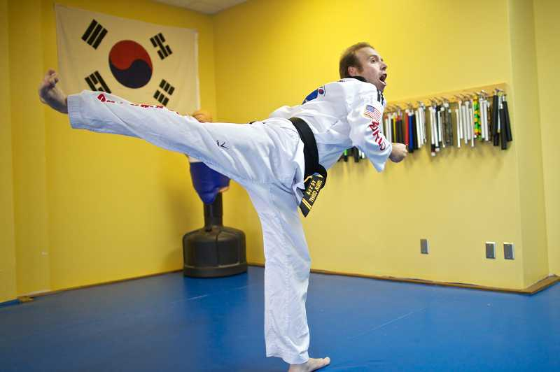 by: JAIME VALDEZ - Torryn Coufal practices his forms at World Championship Taekwondo in Beaverton. An E. coli infection as an infant nearly cost the 30-year-old his life.