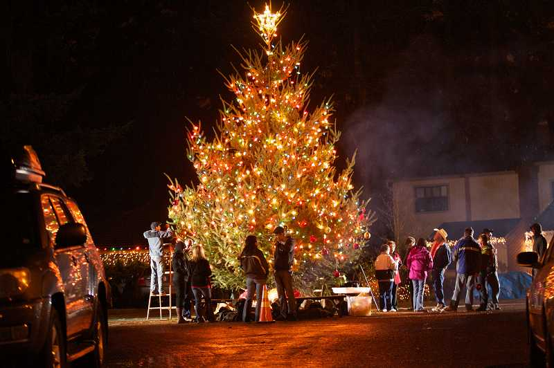 by: JAIME VALDEZ - Neighbors on Southwest Thistlebrook Court in Durham decorate the yearly Christmas tree they erect in the middle of the street. The tree has become a tradition in the tiny town near Bridgeport Village