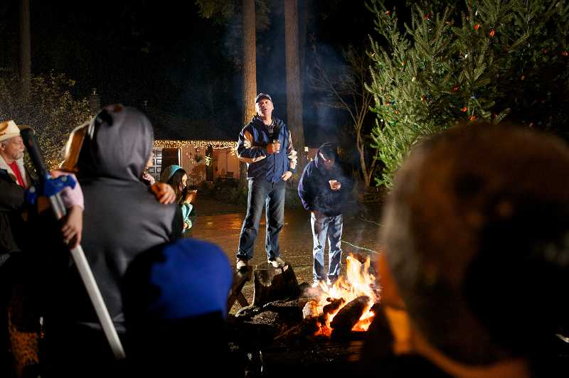 by: VALDEZ - Neighbor Steve Balsiger addresses neighbors on Southwest Thistlebrook Court in Durham before the Christmas tree lights are turned on, Sunday. The neighborhood comes together every year to light a tree in the center of the road.