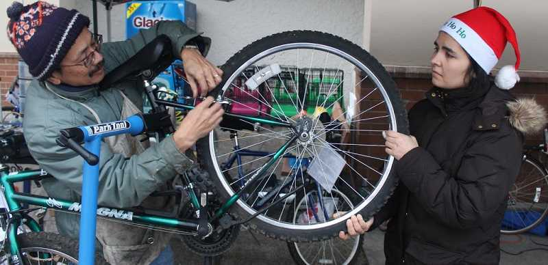 by: SUBMITTED - Volunteers Henry Yuen and Maryna Pecherska work together to refurbish a donated bike during a bike event in Lake Oswego last year.