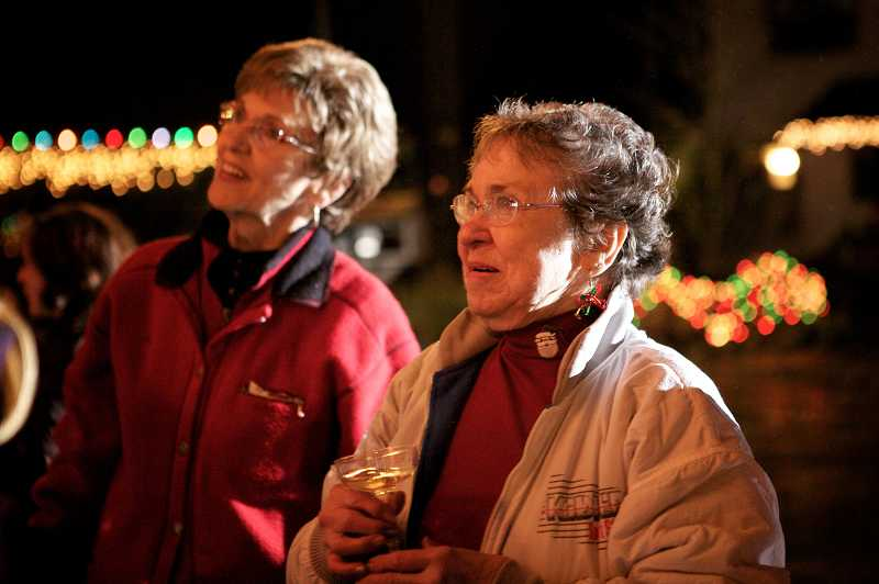 by: JAIME VALDEZ - Marie Hanson and Jean Stephens who have been long-time neighbors on Southwest Thistlebrook Court in Durham, look in awe at the Christmas tree during the neighborhoods annual tree lighting. Stephens house was the first completed house in the cul-de sac.