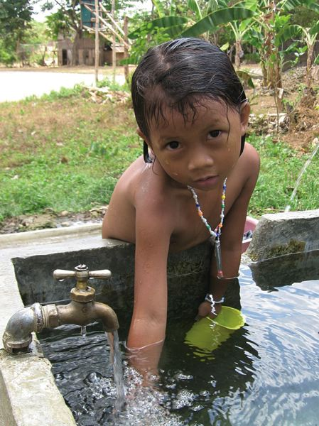 by: PHOTO COURTESY OF AIDFI - Filipino child scoops out clean water provided via a ram pump in Kabankalan City, Negros Occidental, Philippines