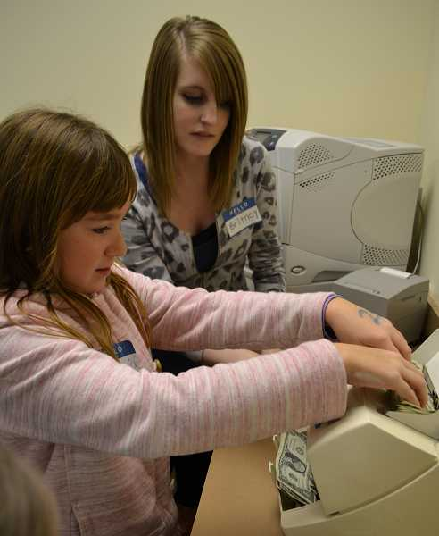 by: SUBMITTED PHOTO  - Girl Scout Isabelle Ansberry operates the MBank paper money counting machine with help from MBank teller Britney King.