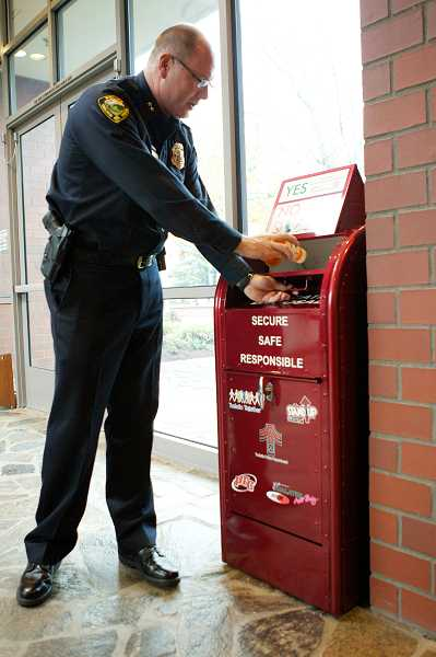 by: TIME PHOTO: JAIME VALDEZ - Tualatin Police Chief Kent Barker drops off outdated prescriptions from home at the police departments new prescription drug drop-off box, which is located in the lobby.