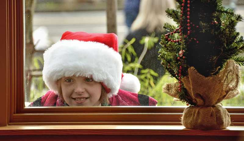by: VERN UYETAKE - West Linn's Kaitlyn Finn, 9, takes a peek at Santa through the window of the Willamette Fire Station following Saturday's holiday parade.