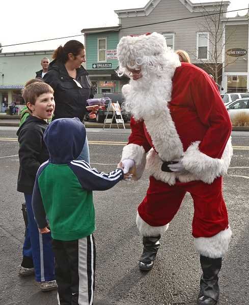 by: VERN UYETKAE - West Linn's Owen Leboeuf, 5, greets Santa outside the fire station.