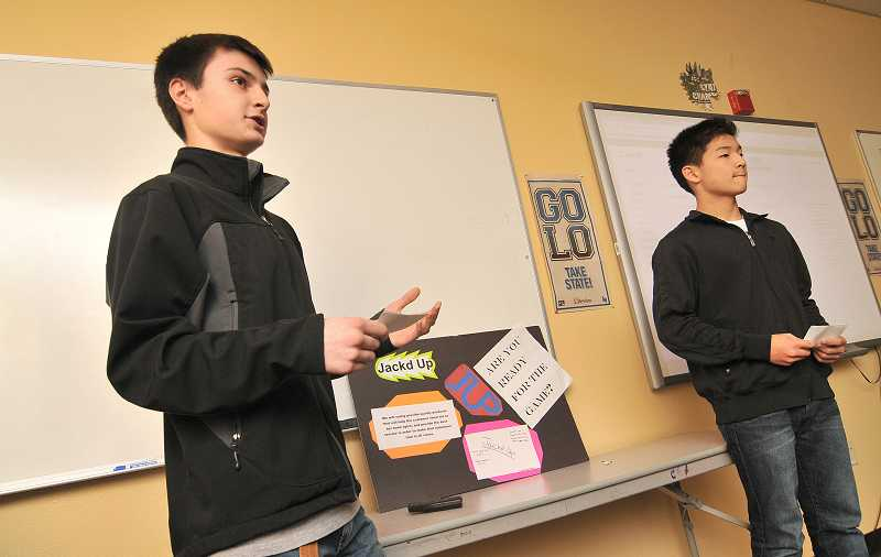 by: REVIEW PHOTO: VERN UYETAKE - Students Nick Gadians, left, and Edward Kang present their product, Jacked-Up, a device that plugs into a cellphone to keep the sports fan up to date with all the latest news about his or her favorite team.