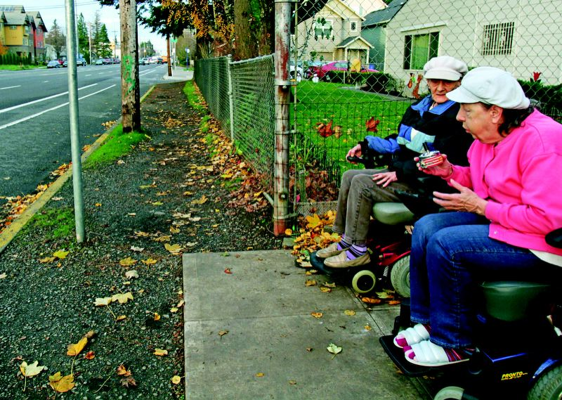 by: TRIBUNE PHOTO: JON HOUSE -  Sisters Maxine Marcum and Aleeta Miner take a smoke break outside the Fir Grove Senior Apartments on Southeast 122nd Avenue. The lack of sidewalks on either side of the property force them to take their motorized wheelchairs onto the busy four-lane street.