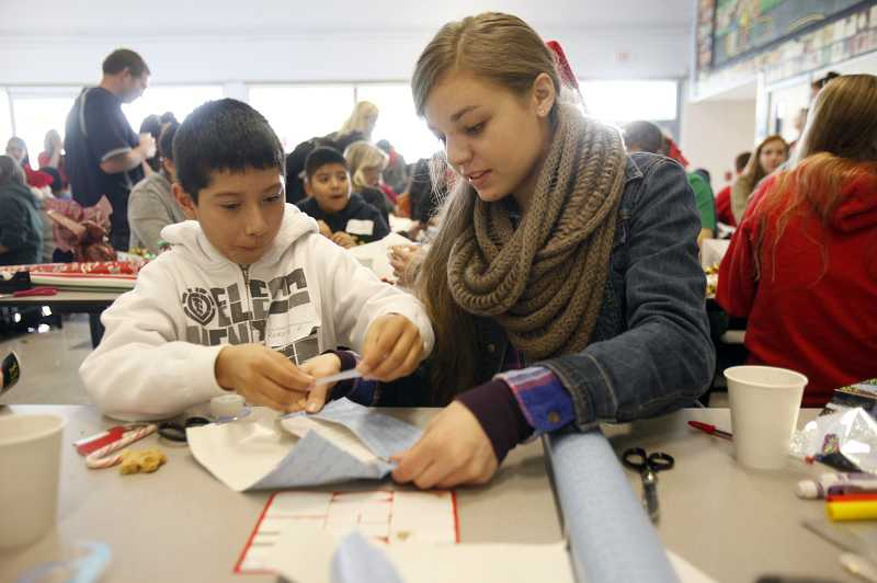 by: TIMES PHOTO: JONATHAN HOUSE - Westview High student Jenny Fandel helps William Walker student Rodolfo Portillo wrap a gift he bought with the $20 Target gift certificate he received. This is the 11th year the two schools have come together for the 'Target Kids' program during the holidays.