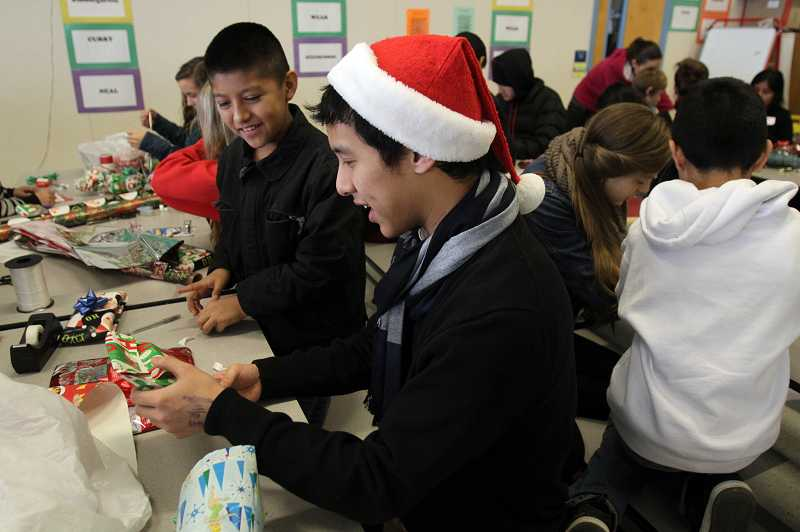 by: TIMES PHOTO: JONATHAN HOUSE - Westview High student Kenneth Do and Luis Germond-Mejia wrap gifts with the $20 gift certificate they spent at Target. Do is the organizer for this year's annual event between the two schools.