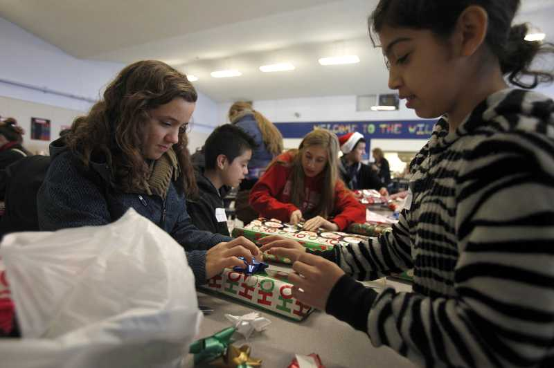 by: TIMES PHOTO: JONATHAN HOUSE - Natalie Kochanowski, left, and Jessica Villa finish up wrapping their presents during the 'Target Kids' event bringing together Westview High and William Walker Elementary students.