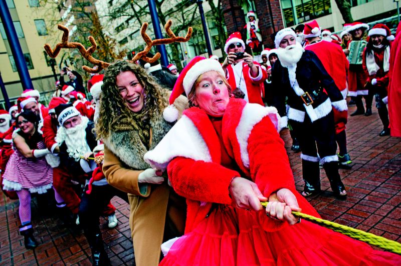 by: TRIBUNE PHOTOS: CHRISTOPHER ONSTOTT - Anne Lise Kelly leads the front of a Santa-on-Santa tug of war during a Portland SantaCon event Dec. 8. The mob of santas stopped to play games along the way, as they marched from bar to bar in downtown Portland.