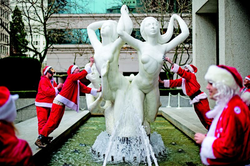 by: TRIBUNE PHOTO: CHRISTOPHER ONSTOTT - Santas climb onto 'The Quest' fountain in downtown Portland, adorning it with ribbons Dec. 8 during a Santacon mission to wrap statues in the city.