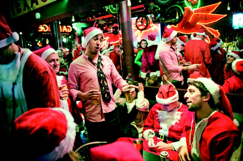 by: TRIBUNE PHOTO: CHRISTOPHER ONSTOTT -  Kelly's Olympian was overrun by more than a hundred Santas during the SantaCon pub crawl Dec. 8.