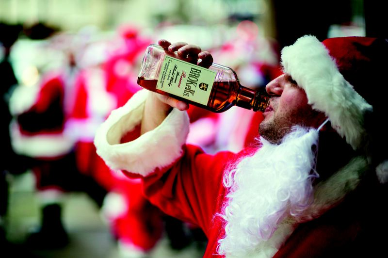 Photo Credit: TRIBUNE PHOTO: CHRISTOPHER ONSTOTT - A 'Santa' takes a big swig of Broker's whiskey outside Kelly's Olympian, the second bar stop on the SantaCon outing Dec. 8.
