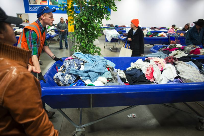 by: TRIBUNE PHOTO: CHASE ALLGOOD - Goodwill employee Jeremiah Corson-Small wheels out a cart of new goods while shoppers eagerly wait for the ok to start digging though the wares. Below, Tina Engelfried searches through the bins at the Goodwill Outlet Store in Hillsboro.
