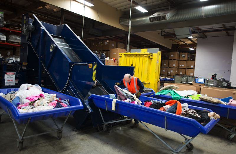 by: TRIBUNE PHOTO: CHASE ALLGOOD - Dan Schmidt loads bedding and clothing into a baler.