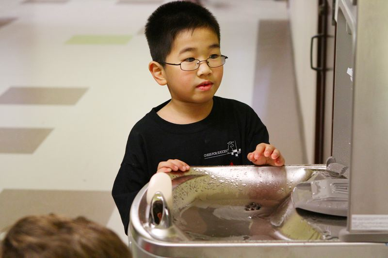 by: DAVID F. ASHTON - First Grader Bao Troung checks out a new drinking fountain at Marysville School.