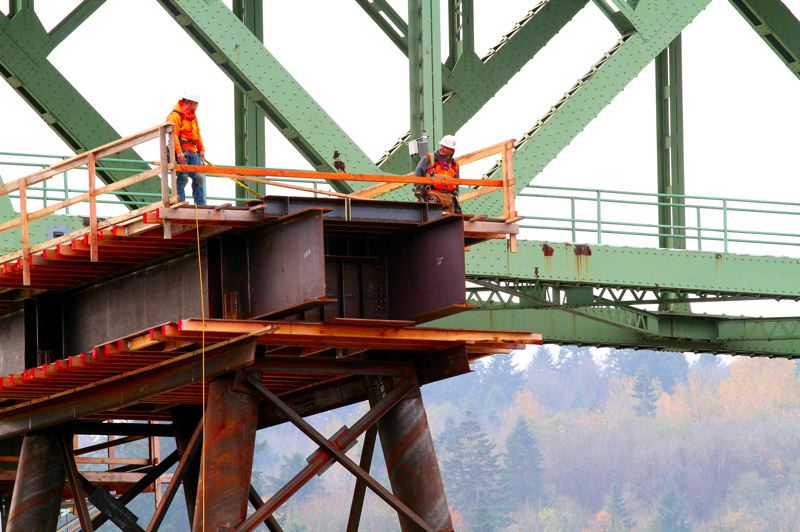 by: DAVID F. ASHTON - On an east-side temporary bridge girder, workers prepare the main span for the 'big slide' in January.