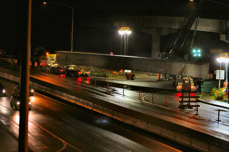 by: DAVID F. ASHTON - A 58-ton girder is in position, and is being made ready to be lifted into place off the split vehicle that drove it here, up Highway 99-E from Harrisburg.