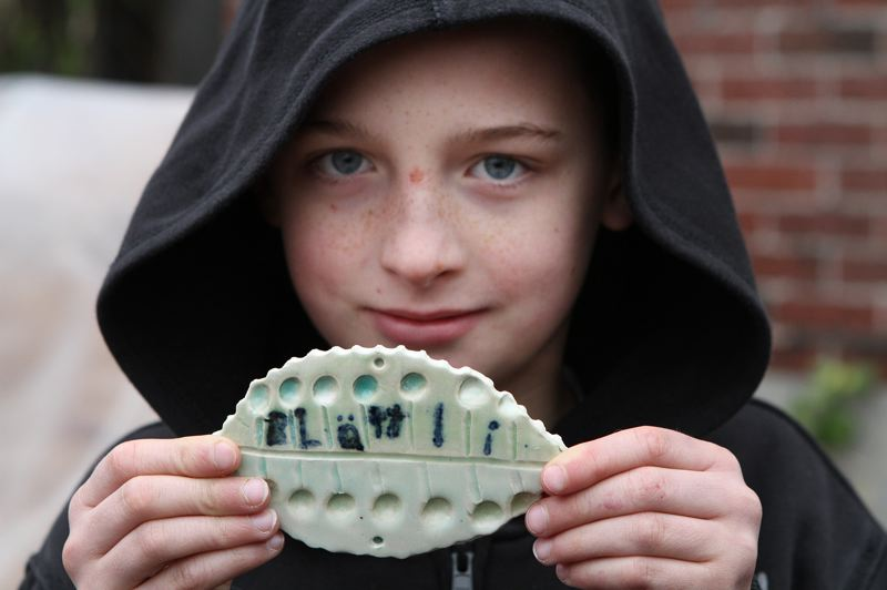 by: DAVID F. ASHTON - Grout School fourth grader Remy Munro shows his leaf tile, which is written in Swiss.