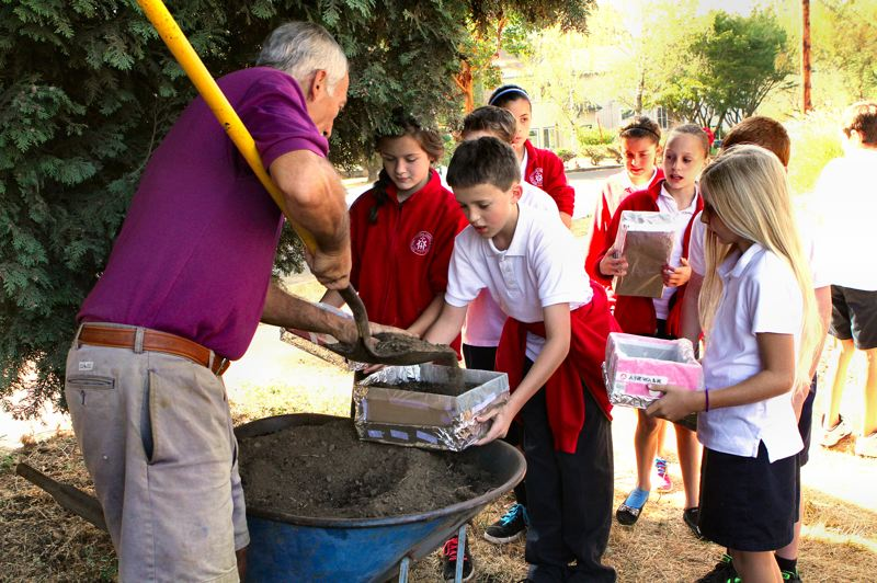 by: DAVID F. ASHTON - Fifth grade Holy Family Catholic School students hold out their 'shoe box garden' boxes, while gardener and teacher Baruch Bashan shovels in the dirt.