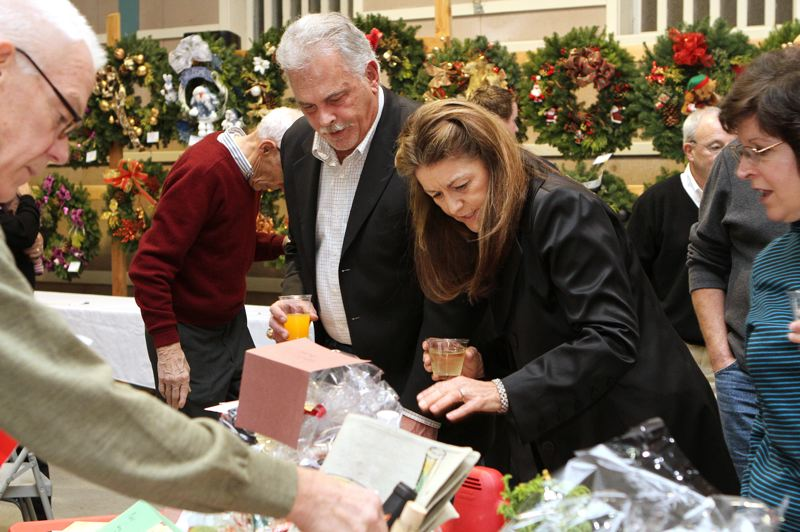 by: DAVID F. ASHTON - John and Jo Zoller examine items in the Rotary Silent Auction.