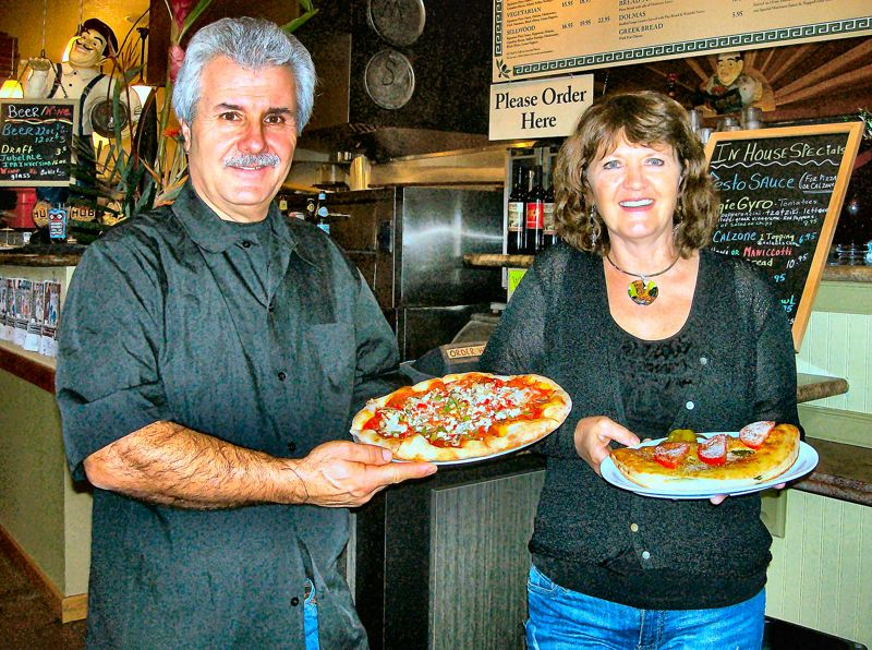 by: RITA A. LEONARD - At OPA Pizzaria on S.E. 13th, owners Tony & Suzi Karagounis display their Greek style pizza, at left, and their football-sized calzoni.