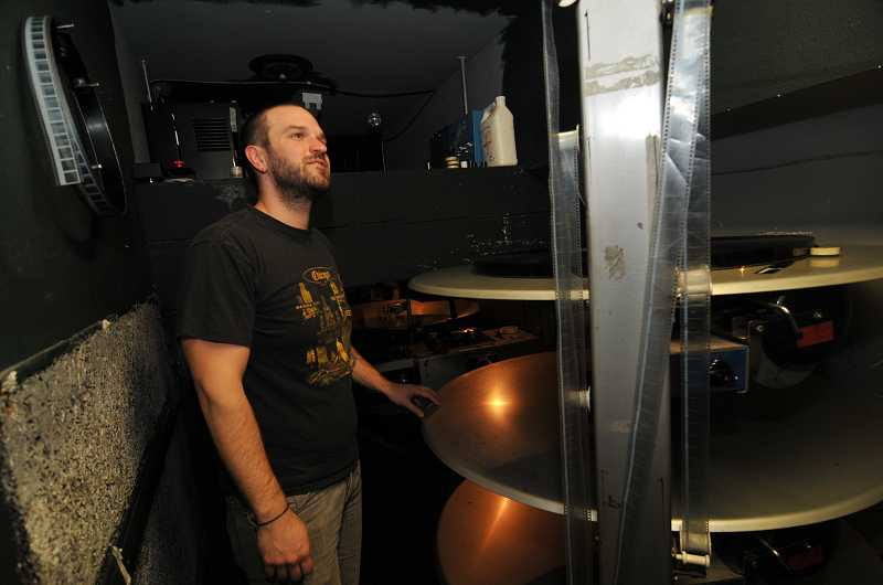 by: REVIEW, TIDINGS PHOTO: VERN UYETAKE - Twin Lakes Theatre projectionist Scott Dunkle places spools of film on the 30-year-old piece of equipment that will soon be obsolete in the digital age.