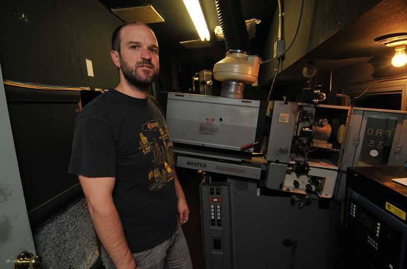 by: REVIEW, TIDINGS PHOTO: VERN UYETAKE - Projectionist Scott Dunkle must cut and splice celluloid film before placing it on the spools.