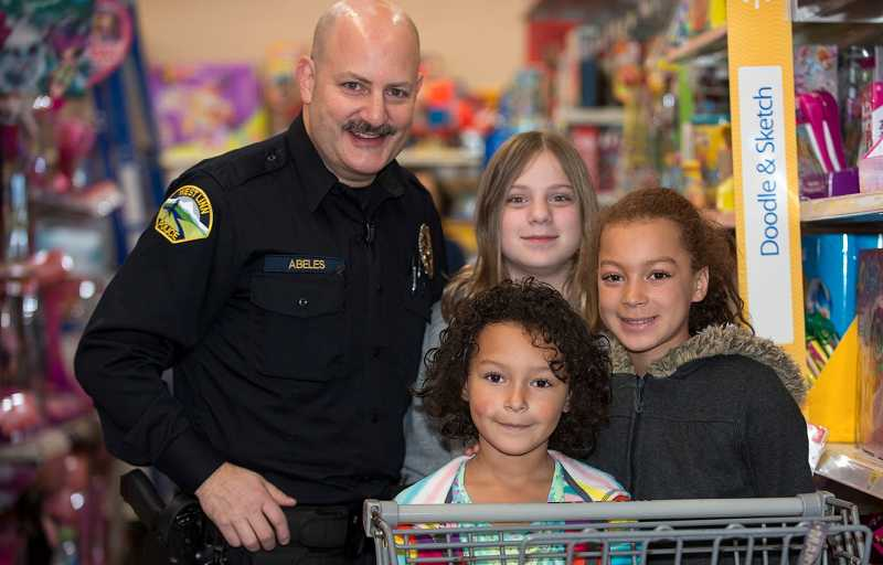 by: JOHN HIGGINS - West Linn Police Officer Jim Abeles is all smiles as he shops with three girls during the event.