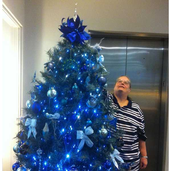 by: SUBMITTED PHOTO: JANICE REYNOLDS - Janice Burton reaches high to adjust an ornament on Moody Blues, her 2012 holiday tree for city hall.