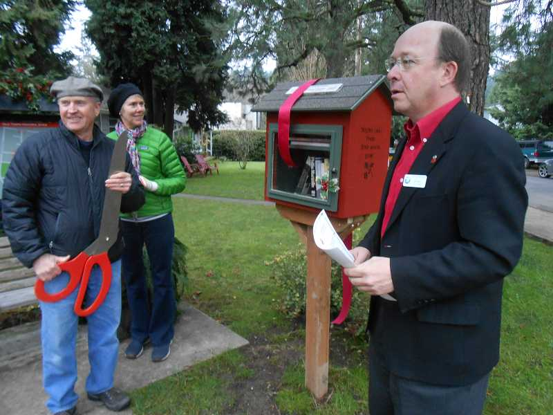 by: REVIEW PHOTO: CLIFF NEWELL - Bill Baars, right, gave the dedication for the Little Library ribbon cutting on Wilbur Street. Helping out were Dick Reamer, wielding the giant scissors, and his wife, Kathi.