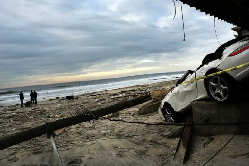by: COURTESY OF MIKE VERKEST - A smashed Porshe in Rockaway Beach, N.Y., sits on the foundation of a home after being flung through a garage during Hurricane Sandy in October.