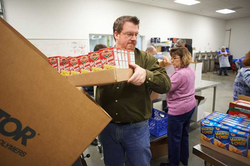by: CHASE ALLGOOD/PAMPLIN MEDIA GROUP - Sherwood Mayor Keith Mays joins other mayors and state representatives in sorting through food donated to the Oregon Food Bank on Dec. 5 in Beaverton.