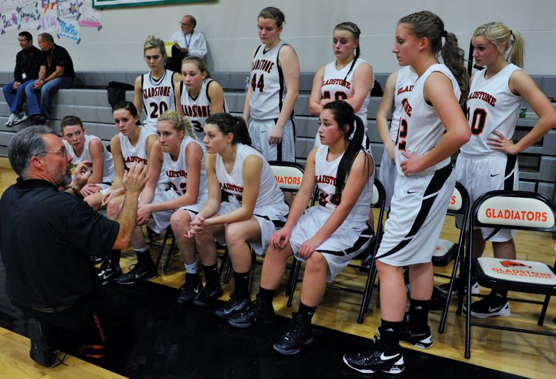 by: JOHN LARIVIERE - Gladstone players listen intently during a timeout in an early-season game with Sisters. Gladstone coach Pat Scott has his Gladiators believing they can be successful this season, despite their youth and inexperience in varsity-level play.