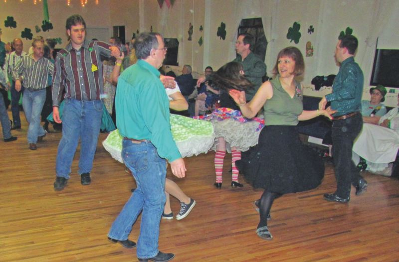 by: PHOTO BY VERN CALDWELL  - Skirts swirl and toes tap as dancers work their way around the square during the 2012 Shamrock Dance with the Oaky Doaks.
