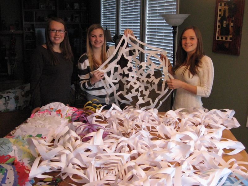 by: RAY PITZ - Kate Palmer, Amy Otis and Hannah Huntington display a portion of at least 1,000 snowflakes Otis helped collect. The snowflakes will be sent to Sandy Hook Elementary School children in Newtown, Conn., to brighten up the atmosphere of their new school.