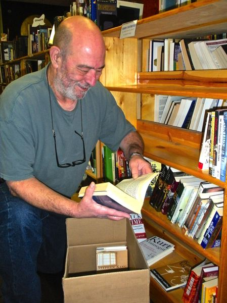 by: POST PHOTO: JIM HART - A smile creeps onto Thom Walkers face as he takes books from the bookcases he built over the years. Walkers business, Some Bookstore in Sandy, is closing Dec. 31.