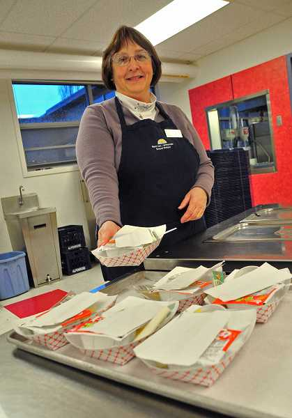 by: TIDINGS PHOTO: VERN UYETAKE - Patty Dehaze, kitchen lead with nutrition services at Sunset Primary School, serves breakfast.