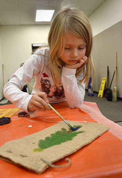 by: TIDINGS PHOTOS: VERN UYETAKE - Third-grader Leanne Beltman put the finishing touches on her gift bag.