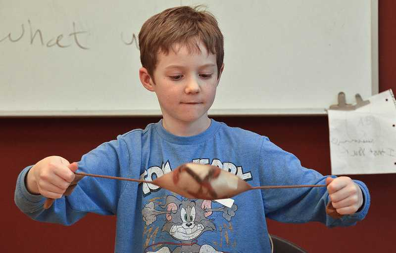 by: TIDINGS PHOTOS: VERN UYETAKE - Second-grader Declan Winder checked out the dish scrubber he made.