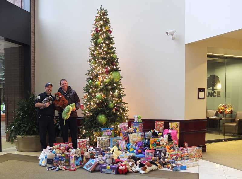by: TAMI HANSEN - Gert Zoutendijk, left, and Karl Ritchey of the Lake Oswego Fire Department were all smiles when they surveyed the results of the Christmas toy drive.